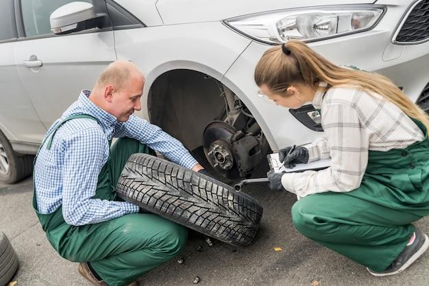 Deux mécaniciens examinant le disque de frein dans la voiture