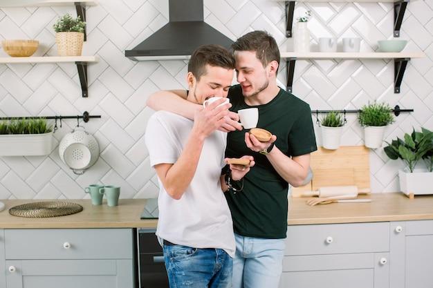 Deux mecs attrayants boivent du café. deux beaux hommes homosexuels à la cuisine à domicile. confort et détente.