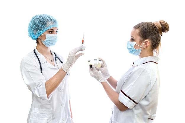 Deux médecins avec ampoules et seringue isolated on white