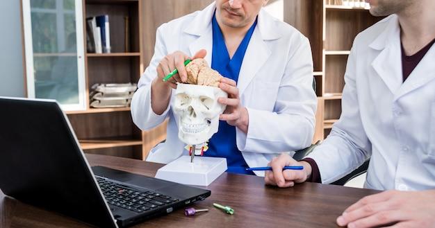 Deux médecins ayant un conseil médical à l'hôpital. discuter des problèmes médicaux avant la chirurgie cérébrale