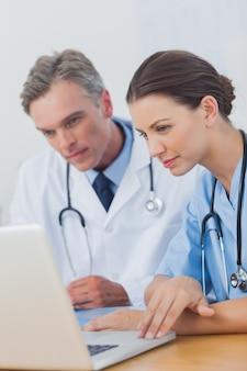 Deux médecins concentrés sur un écran d'ordinateur portable