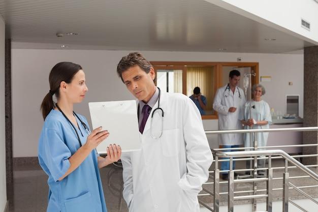 Deux médecins debout dans le hall d'un hôpital tout en regardant les documents
