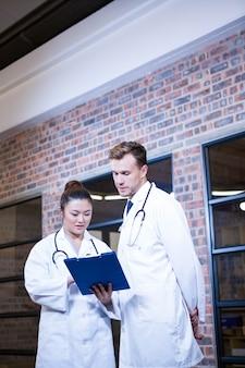 Deux médecins examinant le presse-papiers et discutant près de la bibliothèque de l'hôpital