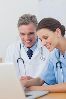 Deux médecins joyeux travaillant sur un ordinateur portable