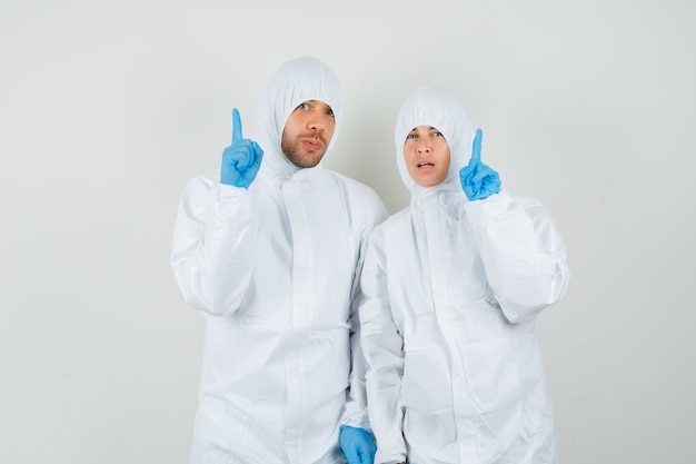 Deux médecins pointant du doigt dans des combinaisons de protection