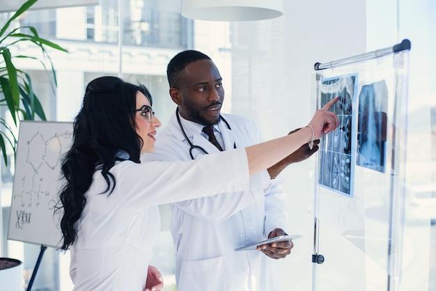 Deux médecins regardent une radiographie et discutent du problème. techniciens médicaux pointant sur la radiographie irm du patient. radiologue vérifiant les rayons x. concept médical et radiologique.