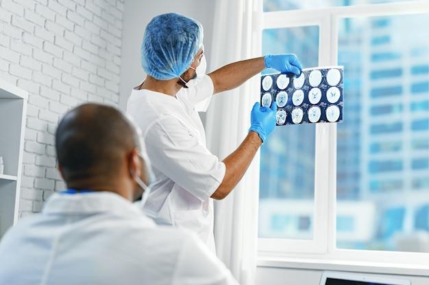 Deux médecins de sexe masculin examinent le scanner cérébral irm d'un patient en cabinet