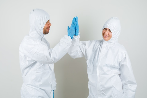 Deux médecins en tenue de protection, gants applaudissant et l'air heureux