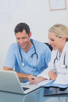 Deux médecins travaillant ensemble sur un ordinateur portable