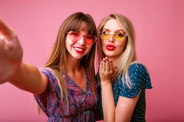 Deux meilleures amies soeur femmes faisant selfie au mur rose, envoyant des baisers aériens et souriant, robes et lunettes de soleil élégantes, humeur printemps-été.