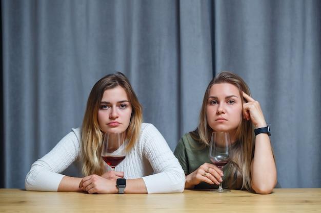 Deux meilleurs amis. jeunes femmes d'apparence européenne ayant une conversation assise à un bureau tenant un verre de vin. belles filles sœurs adorent boire de l'alcool rire joyeux se détendre dans le salon