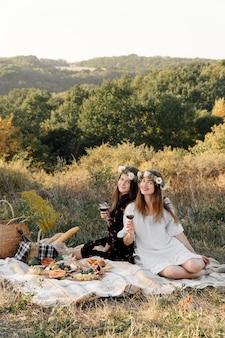 Deux meilleurs amis sur un pique-nique dans le champ portant sur le sourire