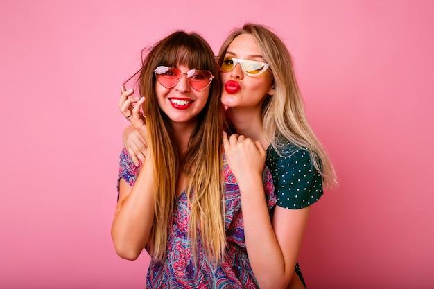 Deux meilleurs amis positifs s'amusant avec des lunettes de soleil