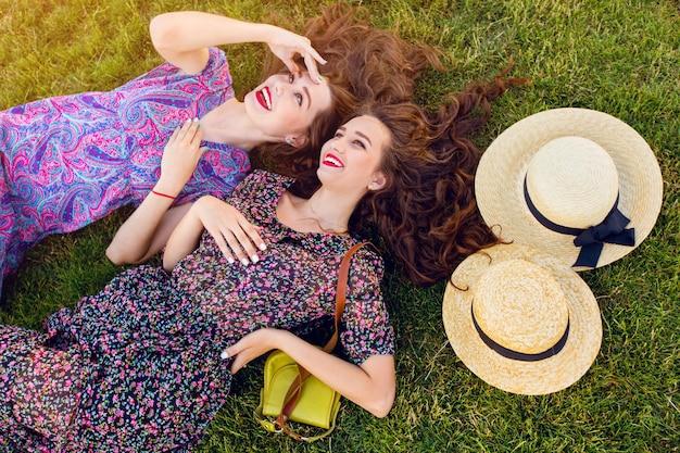 Deux meilleurs amis en robe boho colorée et cheveux bouclés portant sur l'herbe verte