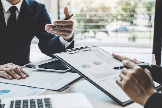 Deux membres de la direction discutent des statistiques financières relatives au succès d'un projet de croissance