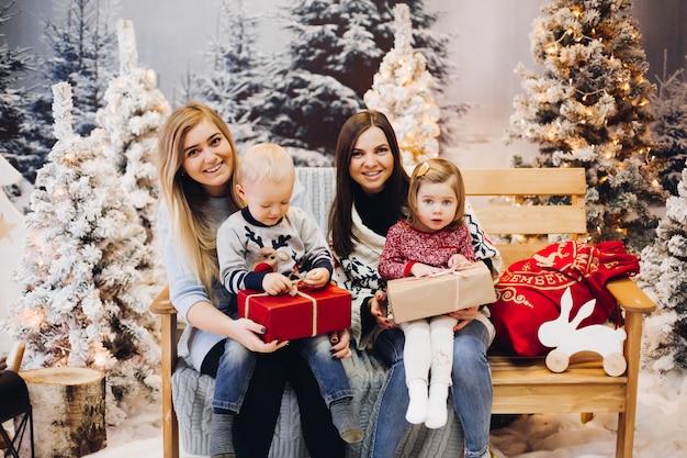 Deux mères assises avec des enfants mignons et tenant des cadeaux de noël