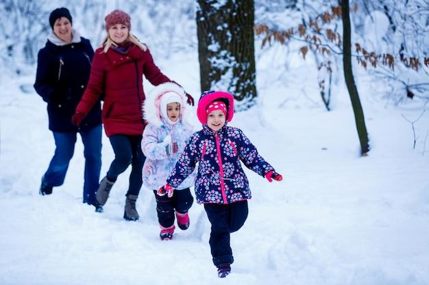 Deux mères et deux filles courir dans une forêt enneigée