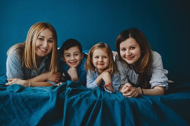Deux mères mentent avec leurs enfants sur le lit bleu