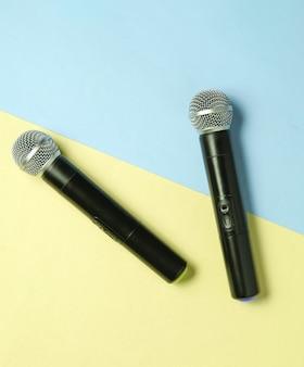 Deux microphone sans fil sur fond pastel jaune bleu. mise à plat. vue de dessus