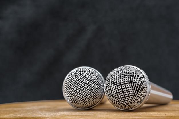 Deux microphones argentés pour l'enregistrement sont en studio sur une table en bois beige
