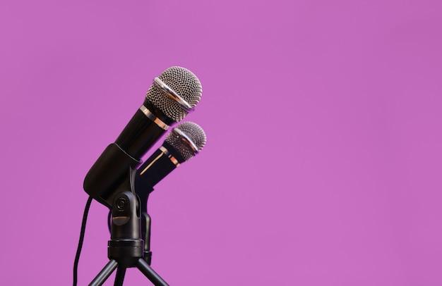 Deux microphones isolés sur fond mauve profond, concept de communication.