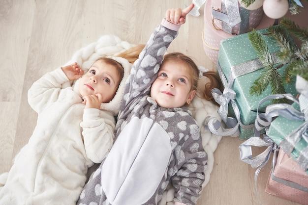 Deux mignonnes petite fille en pyjama gisant sous un arbre de noël parmi des cadeaux