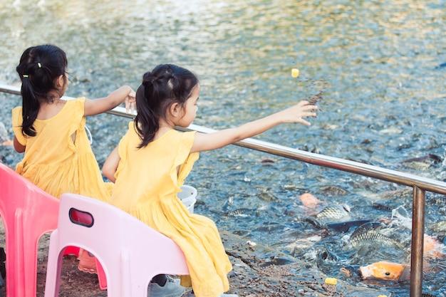 Deux mignonnes petites filles asiatiques s'amuser à nourrir et donner de la nourriture pour pêcher dans l'étang ensemble