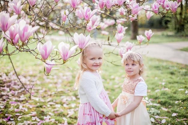 Deux mignonnes petites filles blondes de 3 ans jouent dans le parc près d'un magnolia en fleurs. boire du thé. pâques. printemps.