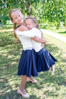 Deux mignonnes petites filles souriantes posant devant leur école.