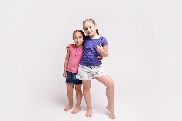 Deux mignonnes petites sœurs d'âges différents souriant montrant le geste de la main pouce vers le haut