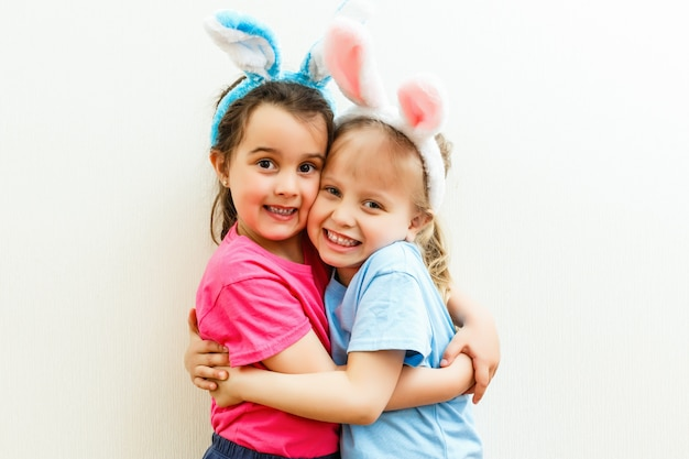 Deux mignonnes petites soeurs portant des oreilles de lapin jouant à la chasse aux œufs à pâques. adorables enfants célèbrent pâques à la maison.