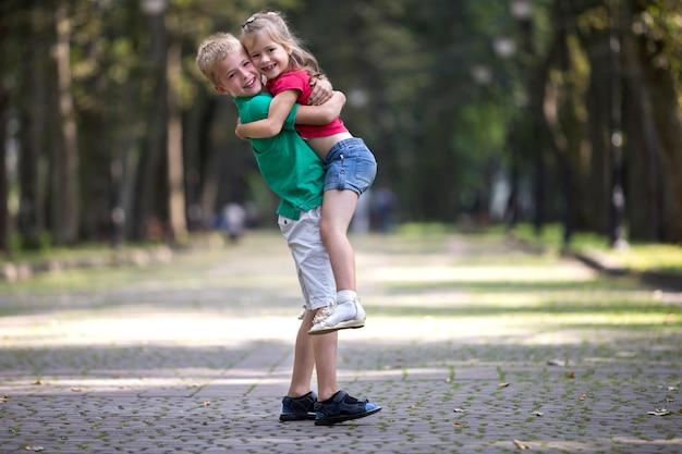 Deux mignons jeunes enfants souriants drôles, fille et garçon, frère tenant sa sœur dans ses bras, s'amusant sur les arbres verts floues ensoleillées du parc. concept de relations de frères et sœurs aimants.