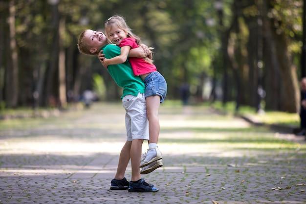 Deux mignons jeunes enfants souriants drôles, fille et garçon, frère tenant sœur dans ses bras, s'amusant sur les arbres verts floues et ensoleillées du parc bokeh. concept de relations de frères et sœurs aimants.