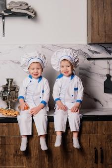 Deux mignons jumeaux assis sur le sol et mangeant joyeusement des aliments sains, jeunes cuisinières
