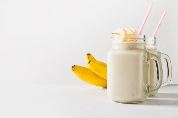 Deux milkshakes à la banane en bonne santé dans un pot mason sur blanc