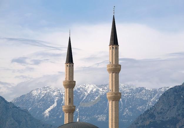Deux minarets musulmans s'élèvent contre des montagnes enneigées imprenables envahies de loin par la végétation sous un ciel bleu serein