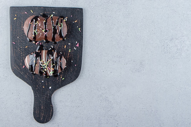 Deux mini gâteaux au chocolat avec des pépites sur une planche à découper noire. photo de haute qualité