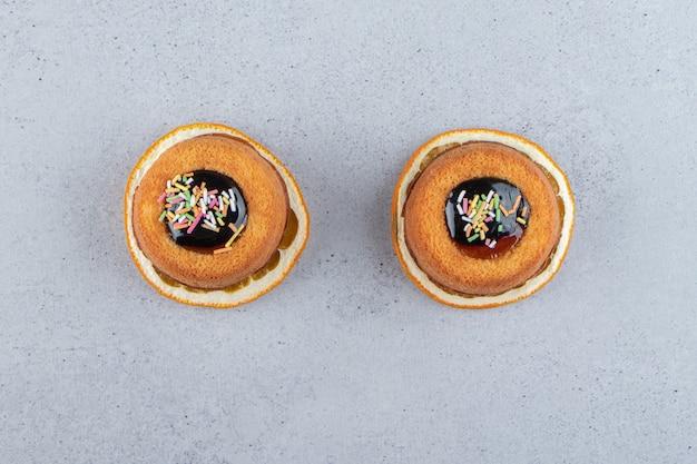 Deux mini gâteaux avec de la gelée placés sur une tranche d'orange. photo de haute qualité