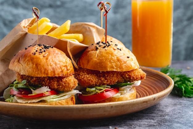 Deux mini hamburgers de nuggets de poulet servis avec des frites dans une boîte en papier