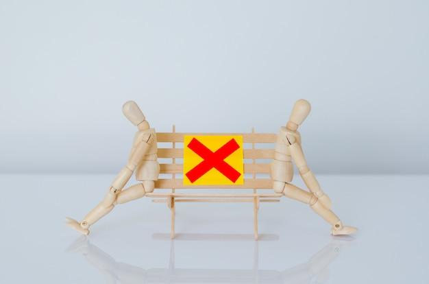 Deux modèles en bois assis sur un banc et gardent une distance avec l'écart pour protéger l'infection du coronavirus ou du covid-19. nouveau concept de distanciation normale et sociale.