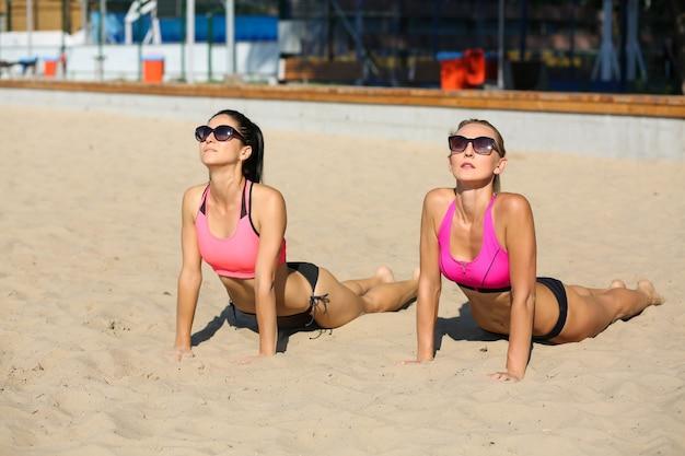 Deux modèles de remise en forme portant des lunettes et un maillot de bain pratiquant le yoga ensemble à la plage