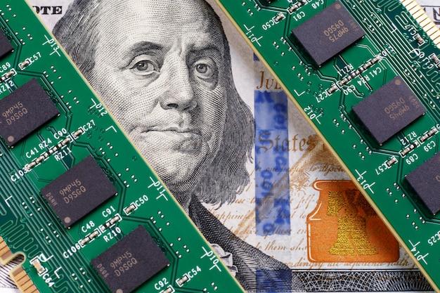 Deux modules de mémoire sur une facture de 100 dollars. franklin regarde avec inquiétude les modules de ram. le concept de remplacer l'argent comptant par de la monnaie électronique.