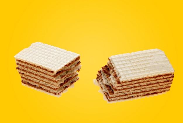 Deux moitiés de gaufre croustillante au chocolat cassé sur un jaune