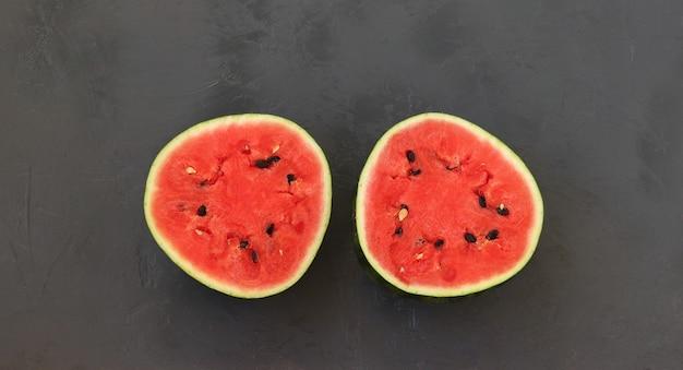 Deux moitiés d'une pastèque mûre laide sur une surface sombre, vue de dessus, format horizontal