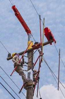 Deux monteurs de lignes utilisent des équipements isolés pour réparer et entretenir les réseaux de distribution haute tension.
