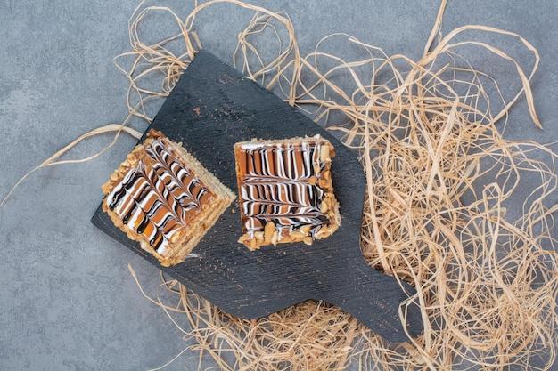 Deux morceau de gâteau sur une planche à découper sombre