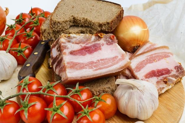 Deux morceaux de bacon salé avec du pain de seigle sur une planche à découper en bois.