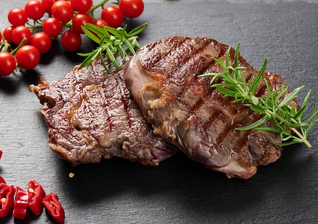Deux morceaux de bœuf ribeye frits sur une ardoise noire, degré de cuisson rare. steak appétissant, gros plan
