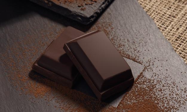 Deux morceaux de chocolat noir sur des plateaux en pierre noire recouverts de poudre de cacao vue de dessus