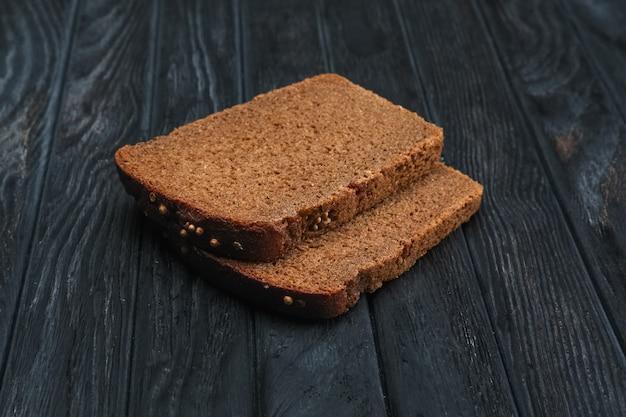 Deux morceaux de pain brun sur une table en bois sombre